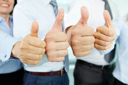 enthusiastic: Close-up of business team holding their thumbs up Stock Photo