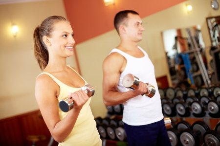 Portrait of pretty girl training in gym with young man near by Stock Photo - 15725928