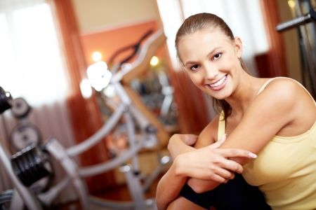 Portrait of pretty girl looking at camera with smile in gym photo