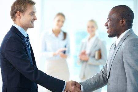 Portrait of happy leaders handshaking and two females applauding on background Stock Photo - 15725943