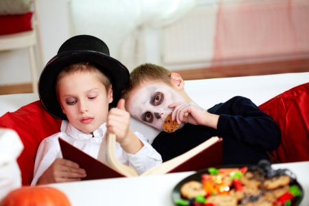 antichrist: two eerie boys reading and eating cookies on Halloween day Stock Photo