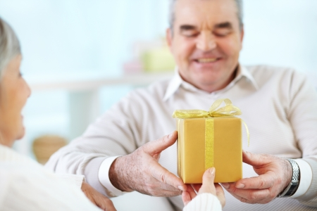 taking a wife: Close-up of mature man taking present from his wife