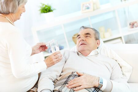 Portrait of mature woman giving tablets to her sick husband at home Stock Photo - 15725946