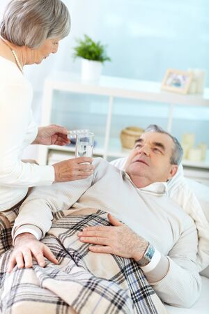 Portrait of mature woman giving tablets to her sick husband at home Stock Photo - 15725906