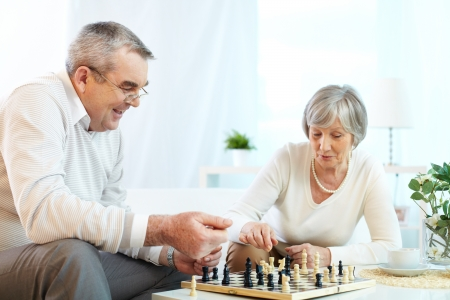 age old: Portrait of senior couple playing chess at leisure