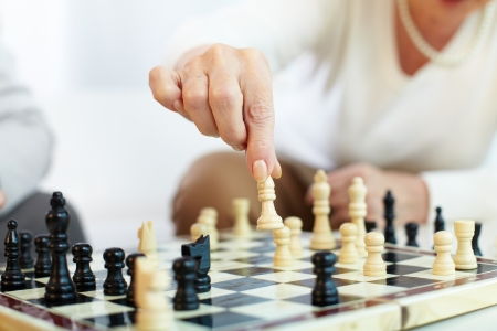 chess player: Portrait of senior human hand holding chess figure