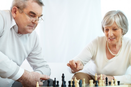 Portrait of senior woman pointing at chess-man while playing chess at leisure with her husband near by photo