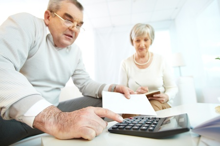 calculadora: Retrato de hombre maduro y su esposa haciendo revisi�n financiera en el hogar Foto de archivo
