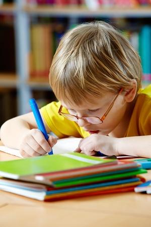 niños estudiando: Retrato de muchacho inteligente dibujo con rotuladores Foto de archivo