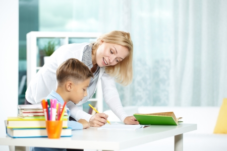schoolwork: Portrait of smart tutor with pencil correcting mistakes in pupil's notebook