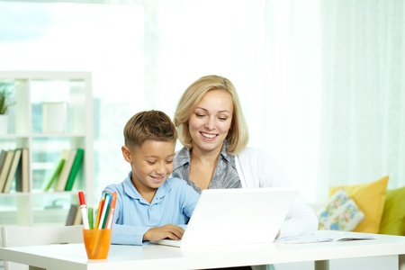 Portrait of pretty tutor and her pupil working with laptop photo