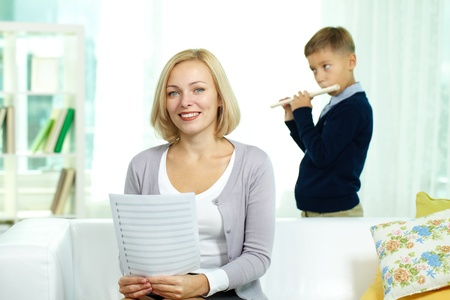 private schools: Portrait of happy tutor with notes looking at camera on background of pupil playing the flute Stock Photo