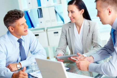 corporate meeting: Image of three confident business partners interacting at meeting