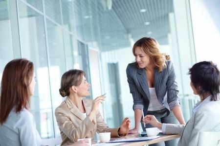 negocios: Imagen de cuatro empresarias interactuando en reunión