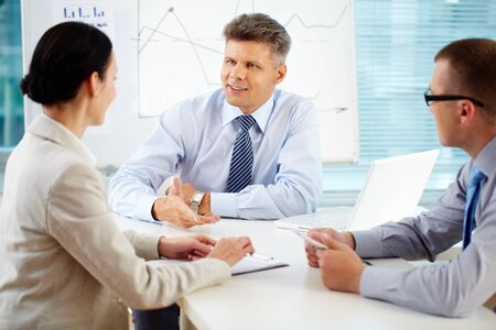 Boardroom meeting: Cheerful team brainstorming while looking for the best business solution Stock Photo