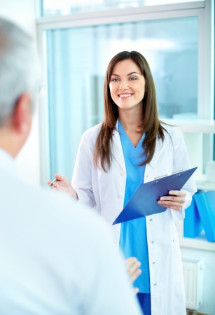 clinician: Portrait of young pretty assistant looking at clinician while interacting with him