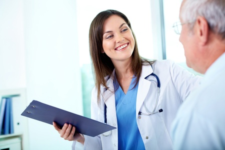 Portrait of young pretty assistant looking at clinician while interacting with him photo