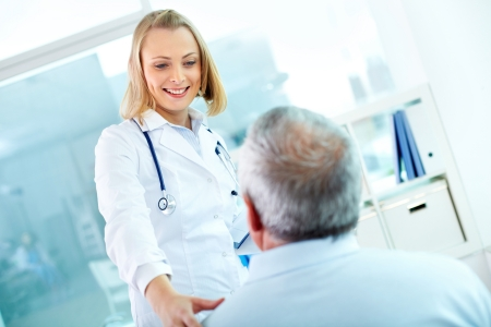 clinician: Portrait of young pretty assistant looking at mature clinician while interacting with him