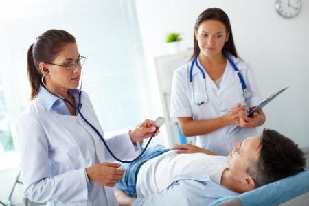 paciente: Retrato de dos mujeres m�dicos mirando paciente durante el tratamiento m�dico en el hospital Foto de archivo