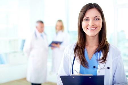 consultant physicians: Portrait of pretty female practitioner looking at camera in working environment Stock Photo
