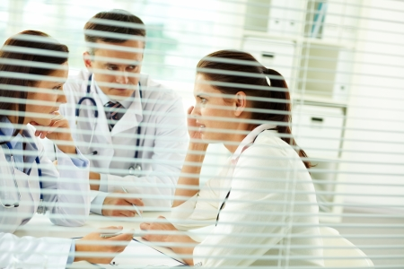 serious doctor: Portrait of confident practitioners consulting patient in medical office