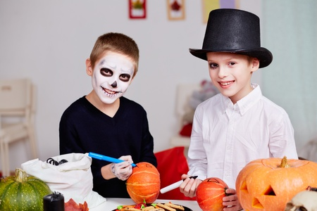 antichrist: Photo of two eerie boys drawing on pumpkins at Halloween table