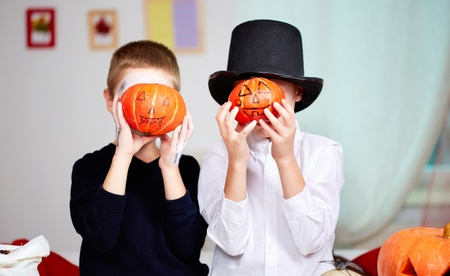 antichrist: Photo of twin eerie boys holding Halloween pumpkins in front of their faces