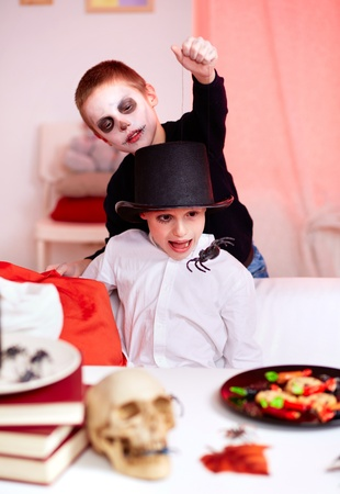antichrist: Photo of evil boy scaring his brother with spider on Halloween