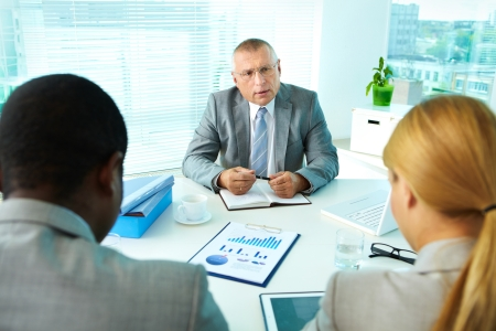 female boss: Portrait of serious boss interacting with his employees Stock Photo