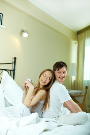 Happy young couple sitting in bed in the morning photo