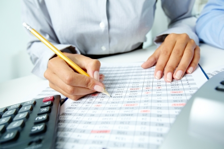 financial planning: Photo of human hands holding pencil and marking numbers in documents  Stock Photo