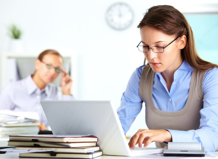 Portrait of pretty secretary typing in office Stock Photo - 15851402