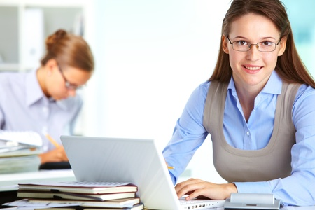 Portrait of pretty secretary looking at camera while typing in office Stock Photo - 15846932