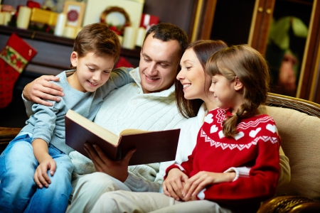 books new books: Portrait of friendly family reading book on Christmas evening