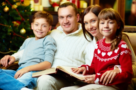 family holidays: Portrait of friendly family with book looking at camera on Christmas evening Stock Photo