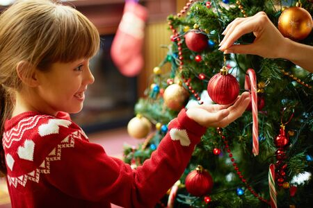 scandinavian christmas: Portrait of happy girl looking at decorative toy ball by Christmas tree Stock Photo