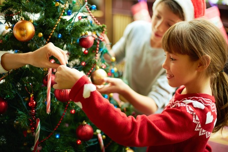 cute christmas: Portrait of happy girl decorating Christmas tree
