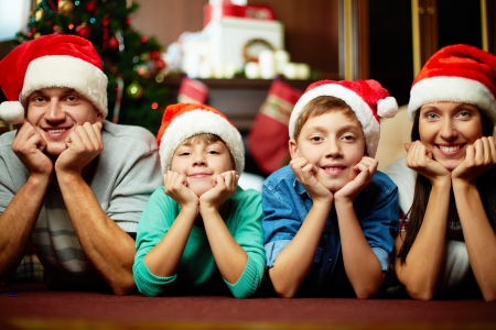 family line: Portrait of friendly family in Santa caps looking at camera on Christmas evening