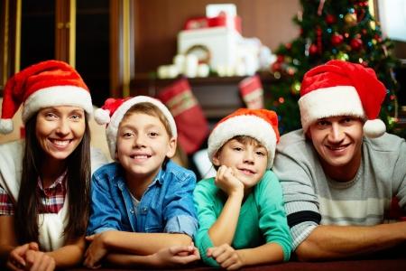 pere noel: Portrait de familles � Santa chapeaux regardant la cam�ra sur le soir de No�l Banque d'images