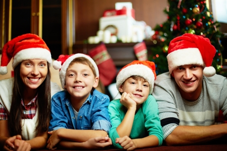 Portrait of friendly family in Santa caps looking at camera on Christmas evening photo