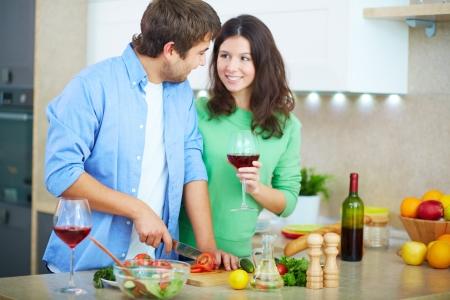 hombre cocinando: Retrato del joven hombre que cocina la ensalada y mirando a su mujer con un vaso de vino tinto en la cocina