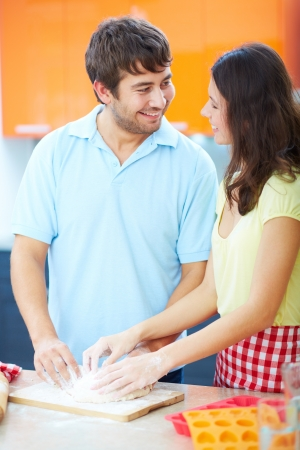Portrait of young man his wife kneading dough in the kitchen  photo