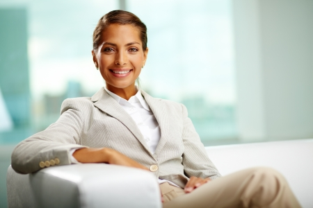 woman in business: Portrait of successful female sitting in office Stock Photo