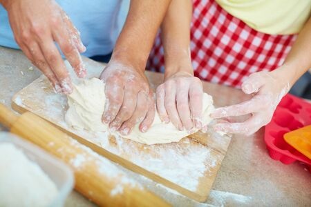 Female and male hands kneading dough in the kitchen  photo