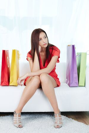 seated: Portrait of stressed shopaholic sitting on sofa surrounded by paperbags