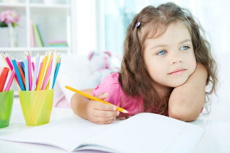 bambini pensierosi: Ritratto di una bella ragazza di disegno con matite colorate