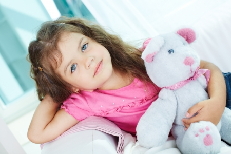 ooking: Portrait of lovely girl with teddybear sitting on sofa and ooking at camera Stock Photo
