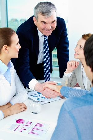 companionship: Foto de hombres de negocios exitosos apretón de manos después del reparto llamativo con socios cercanos por