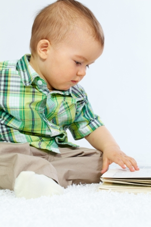 Portrait of calm boy touching page of open book over white background photo
