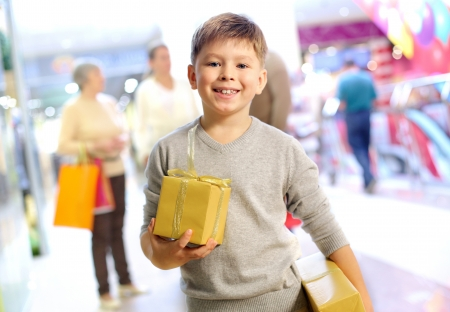 christmas shopping: Portrait of happy child holding gift box with his family on background